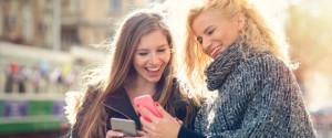 Yahoo - Studie - Teilen für die digitale Beziehungspflege 2 blond teens 2 frauen schauen auf ein Handy und chatten mit männer tvüberregional