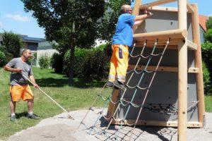 Reilingen, Rund um ein kleines Spielhaus aus Holz sorgen die Bauhofmitarbeiter für einen sicheren Fallschutz