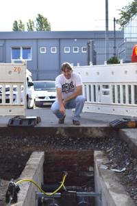 Bild 1, Quelle Stadtwerke Hockenheim,  Martin Kunert von den Stadtwerken Hockenheim zeigt auf das Röntgengerät, mit dem undichte Stellen an einem verlegten Nahwärmerohr an der Theodor Heuss-Realschule entdeckt werden können.